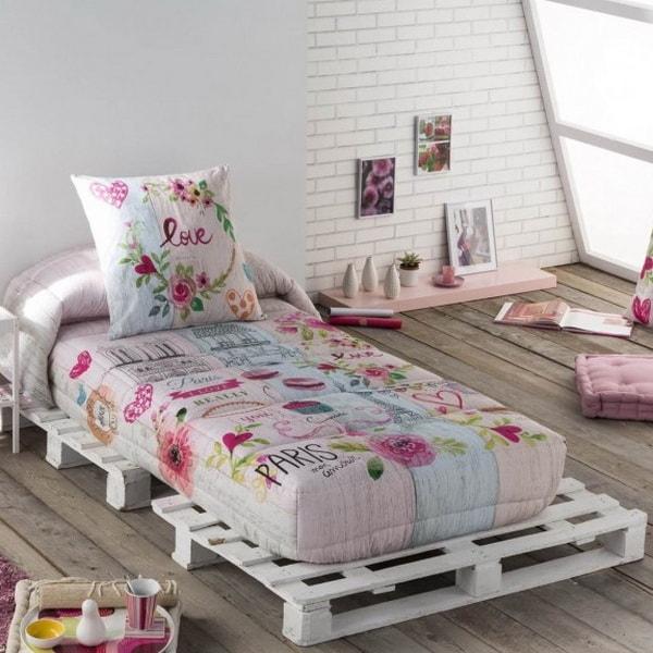 Somier hecho con palets de madera y ropa de cama en tonos rosa